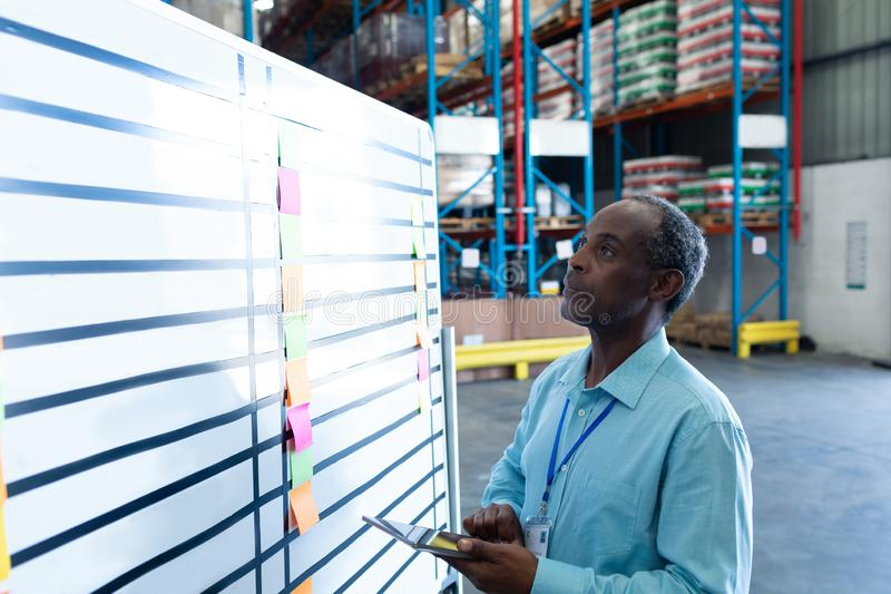 Male supervisor looking at whiteboard in warehouse. Side view of handsome mature African American male supervisor looking at whiteboard in warehouse. This is a royalty free stock photo