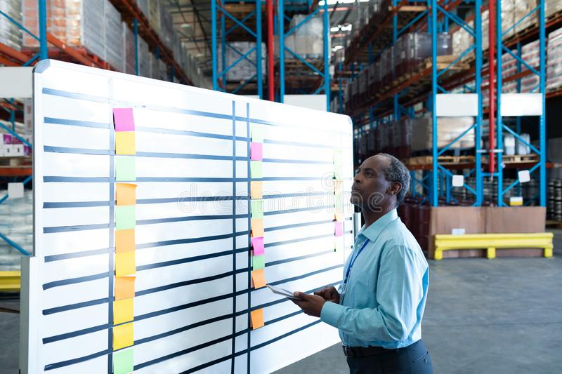Male supervisor looking at whiteboard in warehouse. Side view of handsome mature African American male supervisor looking at whiteboard in warehouse. This is a royalty free stock photography