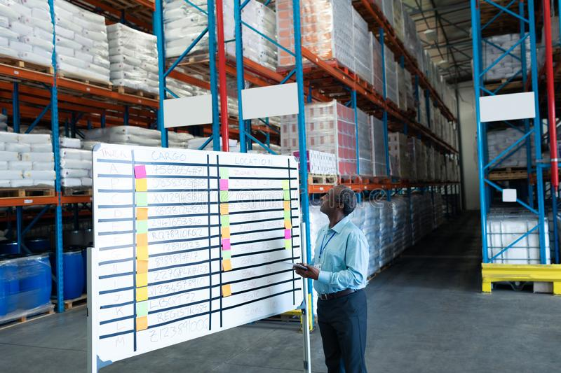 Male supervisor looking at whiteboard in warehouse. Side view of handsome mature African American male supervisor looking at whiteboard in warehouse. This is a royalty free stock image
