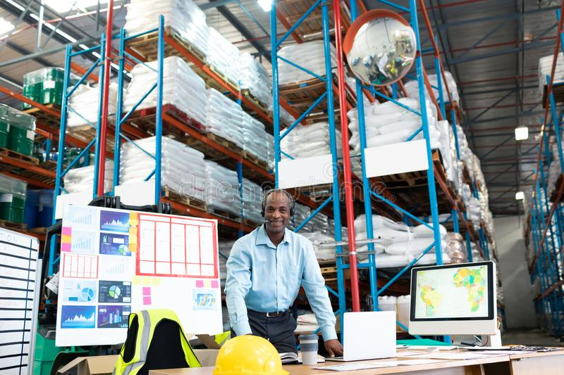 Male supervisor smiling at desk in warehouse. Portrait of handsome mature African-american male supervisor smiling at desk in warehouse. This is a freight royalty free stock photography