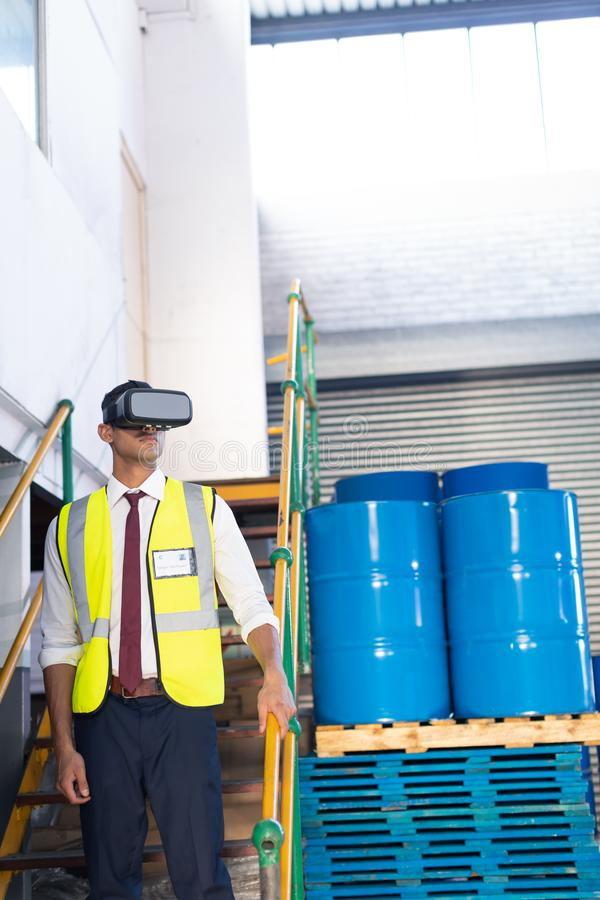 Male supervisor using virtual reality headset in warehouse. Front view of young Caucasian male supervisor using virtual reality headset in warehouse. This is a royalty free stock images