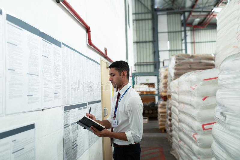 Male supervisor writing on a diary in warehouse. Side view of young Caucasian male supervisor writing on a diary in warehouse. This is a freight transportation royalty free stock photos