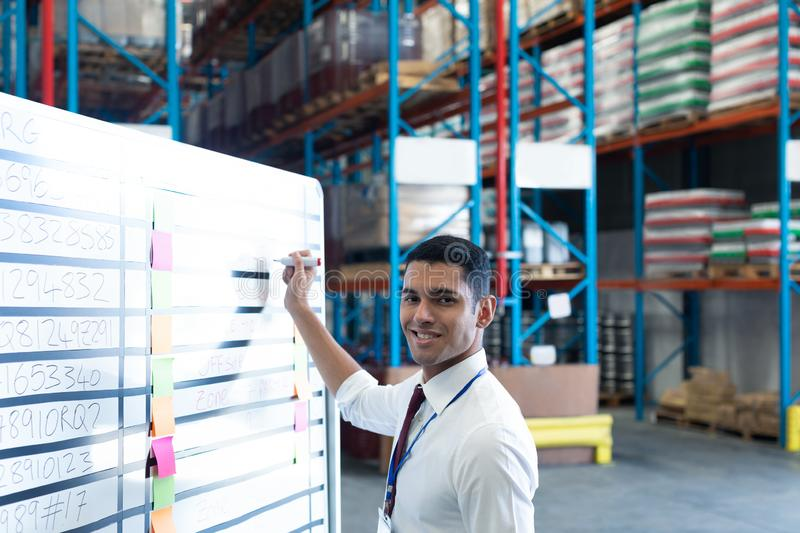 Male supervisor writing on whiteboard in warehouse. Portrait of handsome young Caucasian male supervisor writing on whiteboard in warehouse. This is a freight stock image