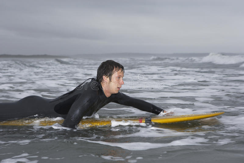 Male Surfer Paddling On Surfboard In Water At Beach. Side view of male surfer paddling on surfboard in water at beach stock photos