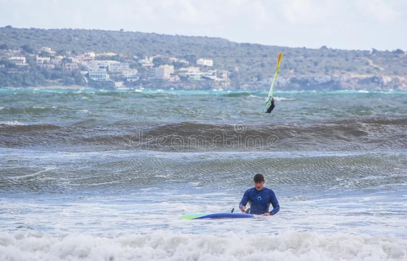 Male surfer takes a fall in green waves stock images