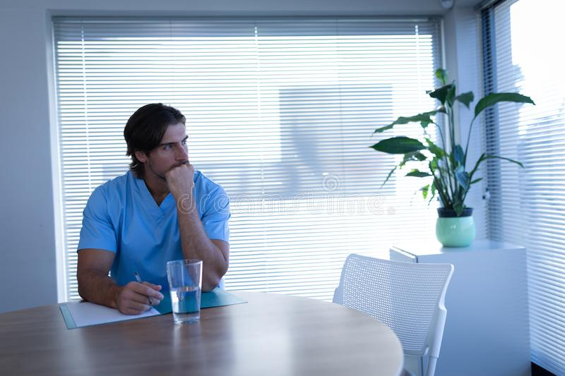 Male surgeon sitting on chair stock image