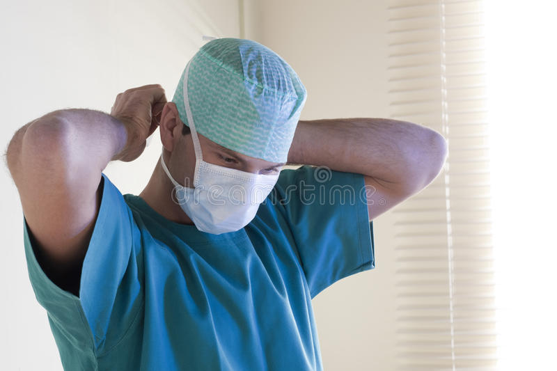 Male surgeon tying mask stock image