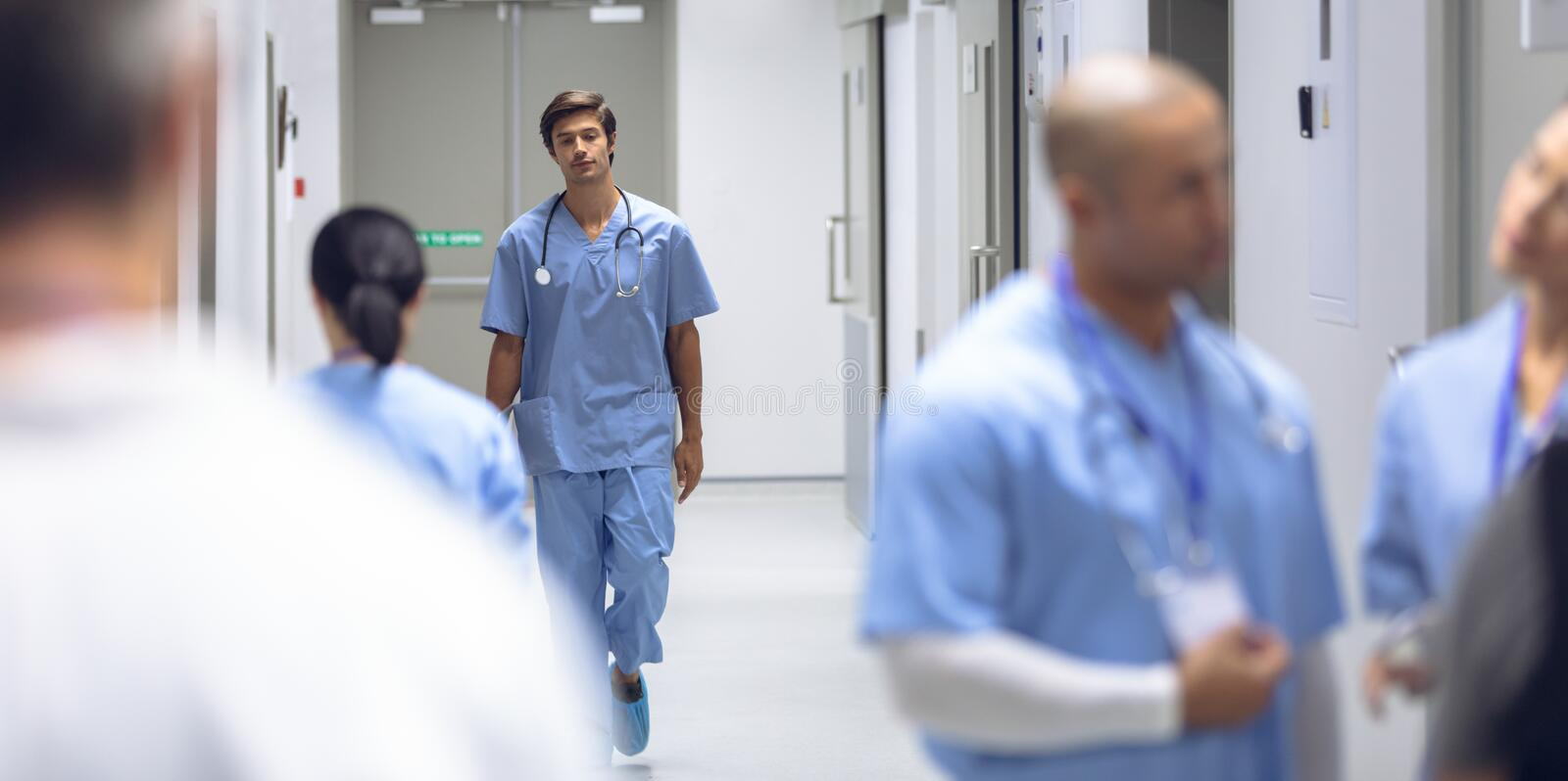 Male surgeon walking in corridor at hospital stock image