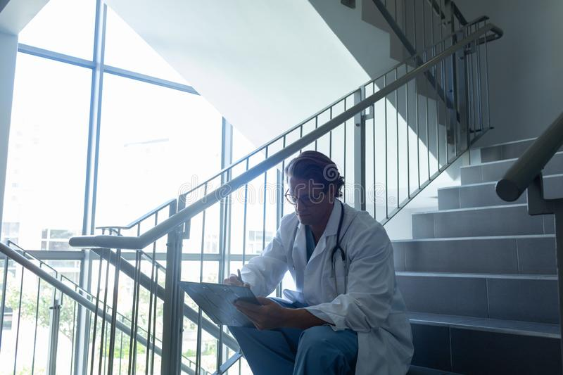 Male surgeon writing on clipboard while sitting on stairs at hospital royalty free stock photos