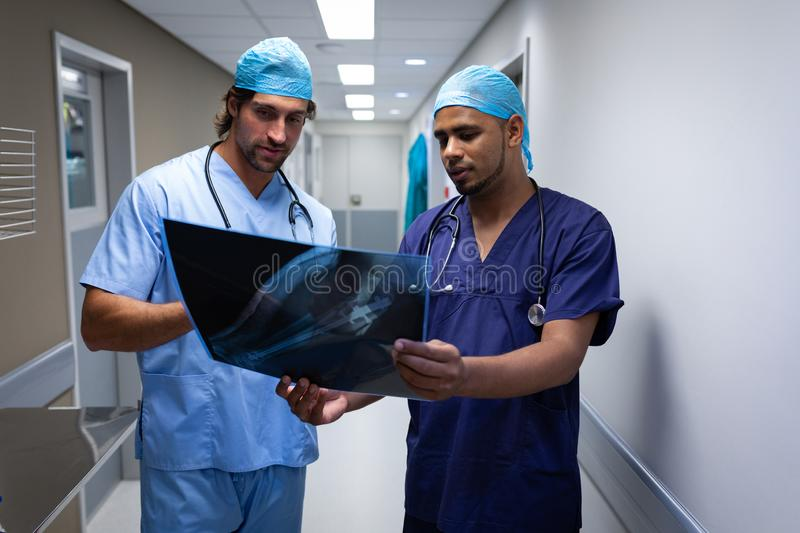 Male surgeons discussing over x-ray report at hospital corridor stock photography