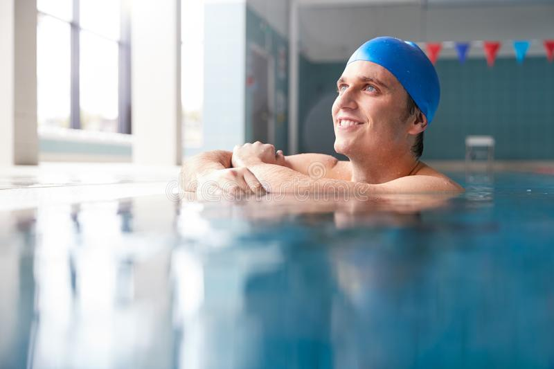 Male Swimmer Wearing Hat And Goggles Training In Swimming Pool stock photos