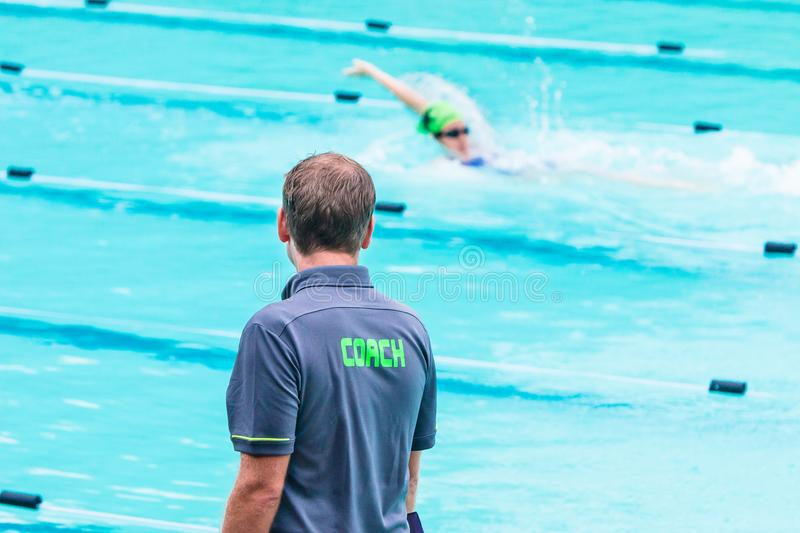 Male swimming coach standing by the swimming pool in the rain wa royalty free stock photo