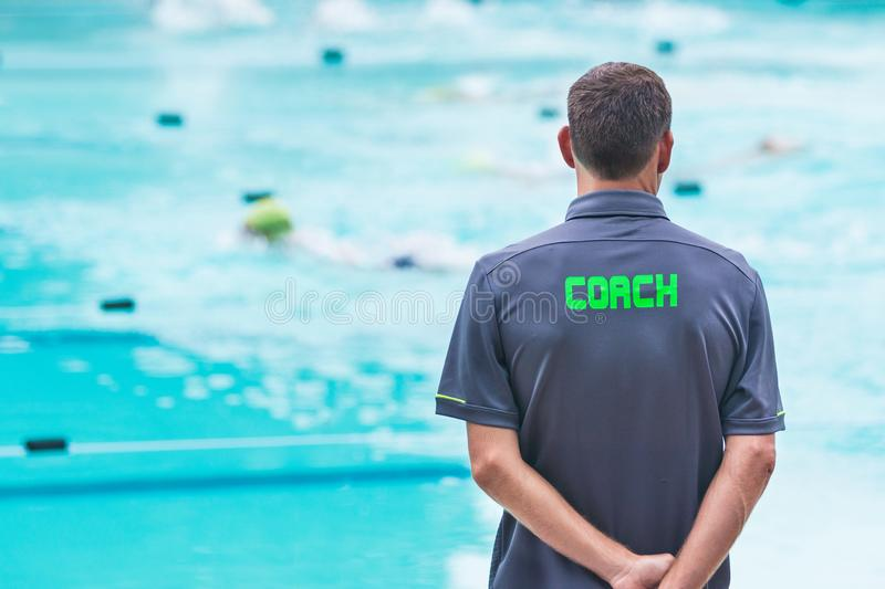 male swimming coach standing by the swimming pool watching swimmers racing by stock images