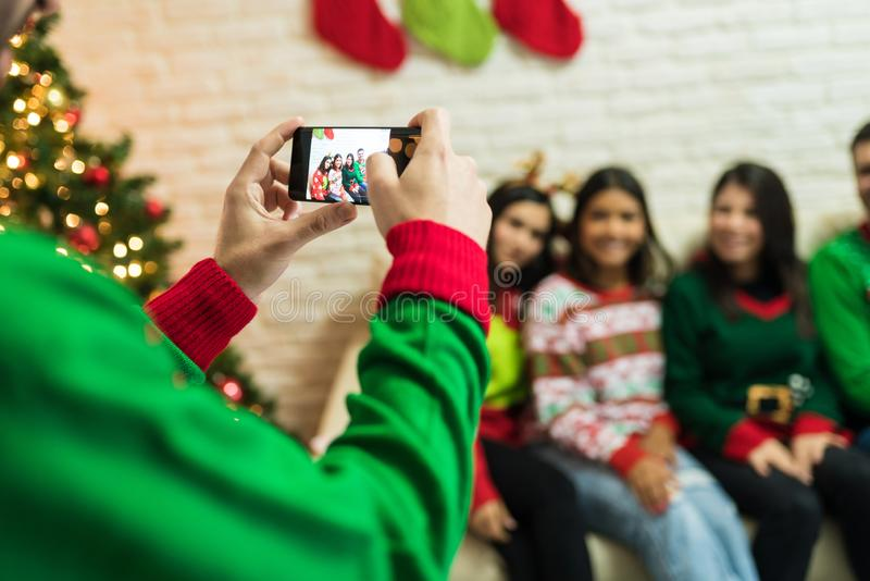 Male Taking Photos Of Friends On Christmas Night At Home stock photography