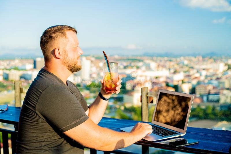 Male talking on the phone and working on a laptop in a rooftop cafe with a panoramic view. man drinking a cocktail and stock image