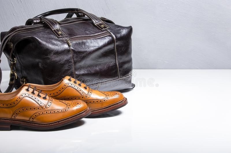 Male Tanned Full Broggued Oxford Calf Leather Shoes. Along With Dakr Brown Leather Travel Bag on White Surface. Horizontal Image Orientation stock photo
