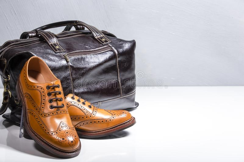 Male Tanned Full Broggued Oxford Calf Leather Shoes Along With D. Akr Brown Leather Travel Bag on White Surface. Horizontal Image royalty free stock photography