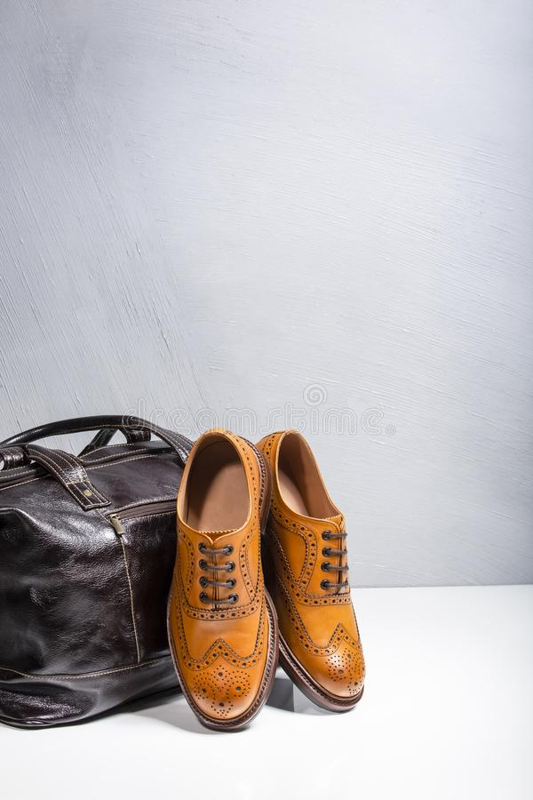 Male Tanned Full Broggued Oxfords. Footwear and Accessories Concepts. Male Tanned Full Broggued Oxford Calf Leather Shoes Along With Dakr Brown Leather Travel royalty free stock images