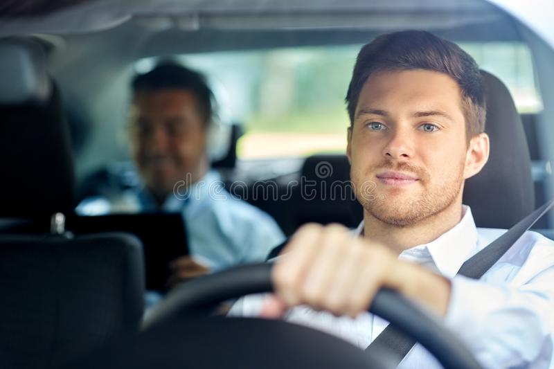 Male taxi driver driving car with passenger. Transport, people and taxi concept - male driver driving car with passenger royalty free stock photos