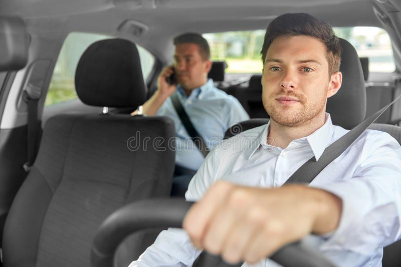 Male taxi driver driving car with passenger. Transport, vehicle and taxi concept - male driver driving car with passenger royalty free stock photography