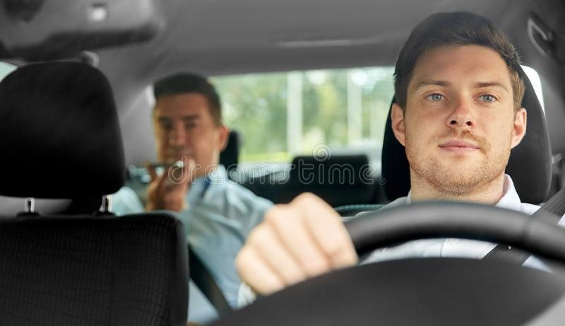 Male taxi driver driving car with passenger. Transport, vehicle and taxi concept - male driver driving car with passenger royalty free stock images