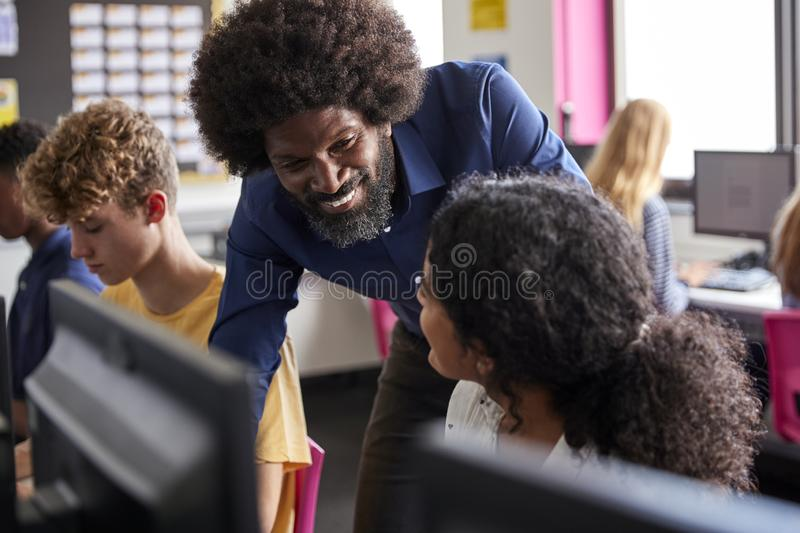 Male Teacher Helping Teenage Female High School Student Working In Computer Class stock photo