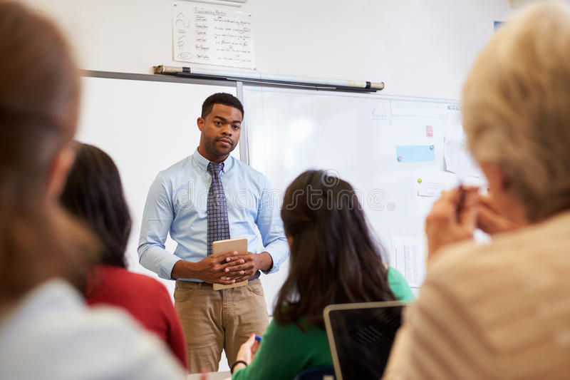 Male teacher listening to students at adult education class royalty free stock photo