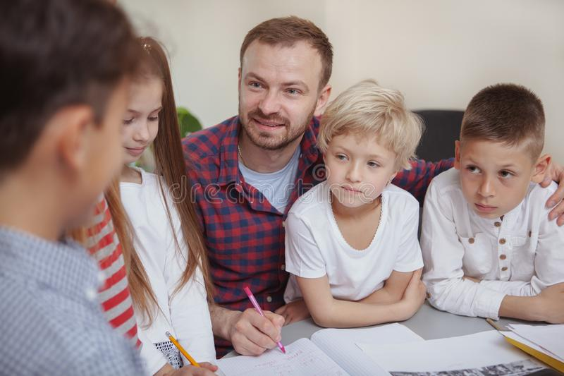 Male teacher working with children at preschool. Cheerful male teacher smiling at his little students listening to their presentation on the lesson. Group of royalty free stock photo