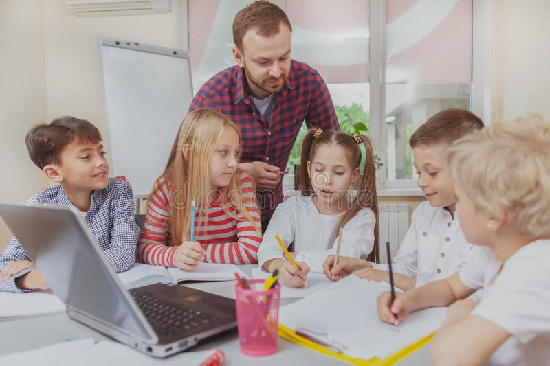 Male teacher working with children at preschool. Elementary school teacher enjoying working with cheerful little kids. Group of preschool children talking during royalty free stock photos