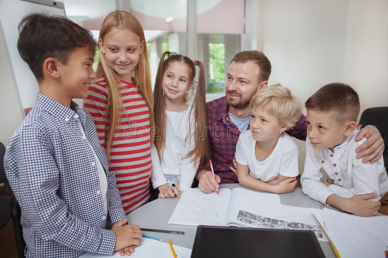 Male teacher working with children at preschool. Young charming boy talking during lesson at elementary school, his classmates and teacher listening attentively stock photo