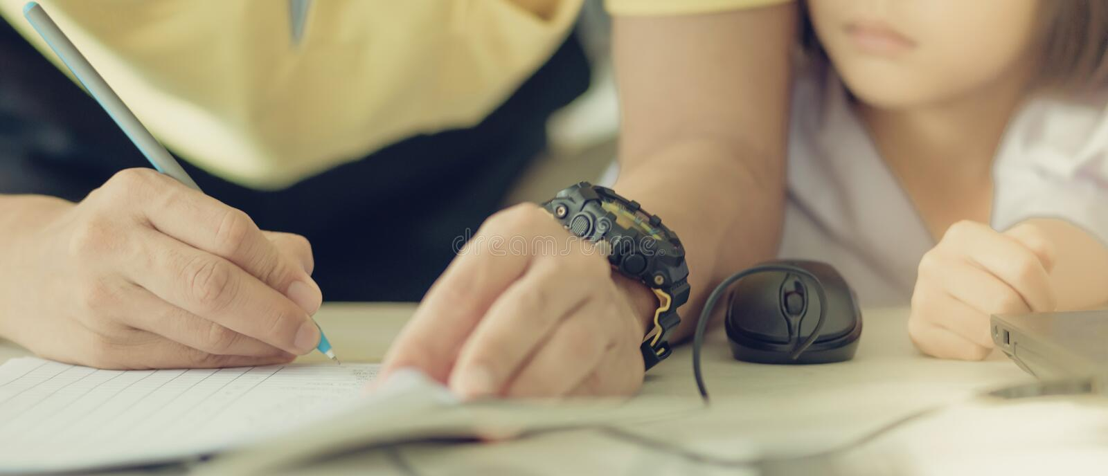Male teacher in yellow shirt going around class, helping and che stock photo
