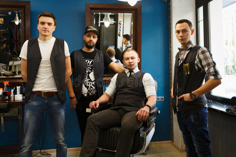 Male team of barbers at modern barbershop stock photography