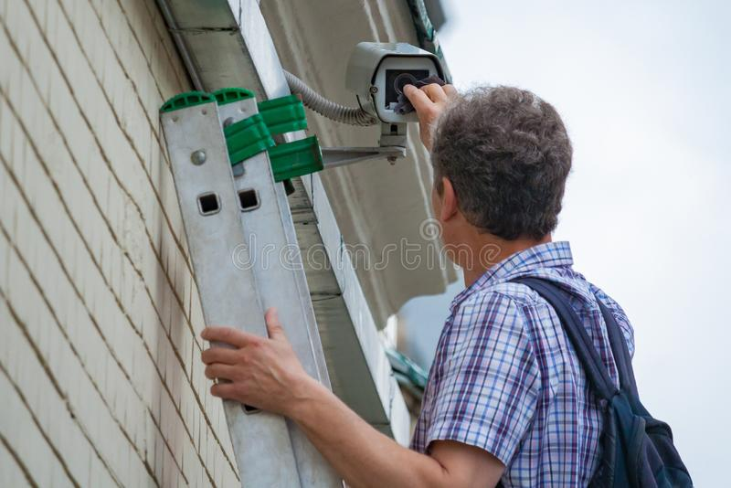 A male technician is doing maintenance work by inspecting and cleaning an outdoor security stock image