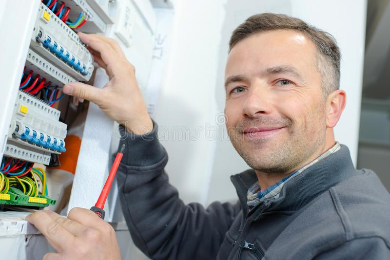 Male technician examining fusebox royalty free stock photography