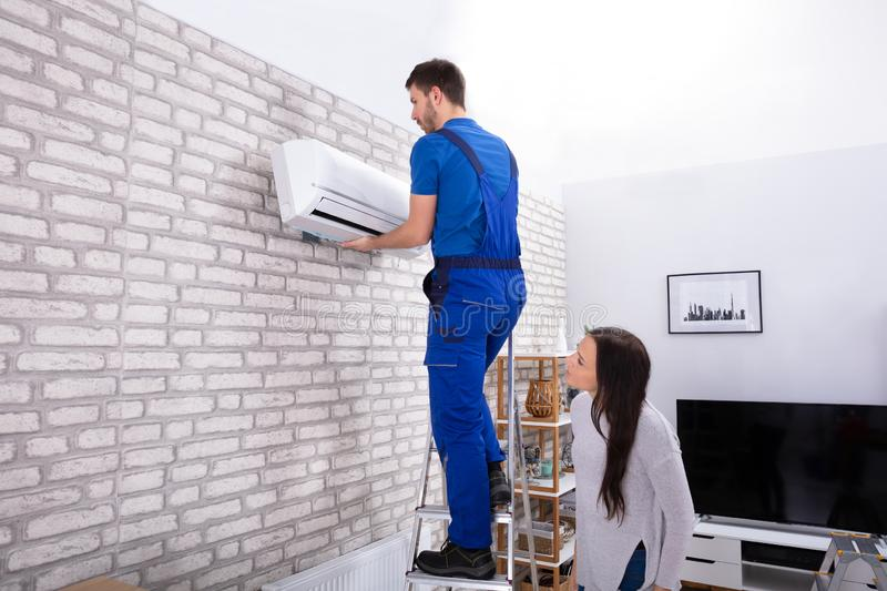 Male Technician Fixing Air Conditioner On Wall. Young Woman Looking At Male Technician Fixing Air Conditioner On Brick Wall stock image