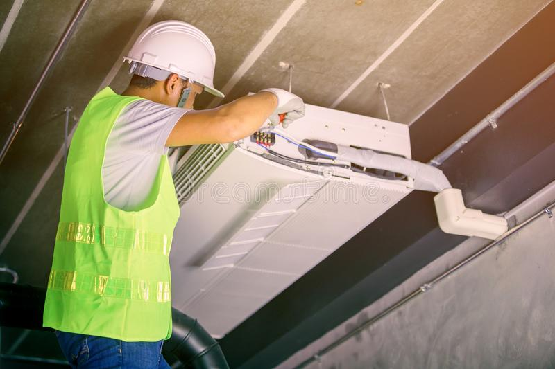 Male Technician Repairing Air Conditioner. In uniform stock photo