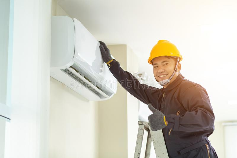 Male technician repairing air conditioner safety uniform indoors royalty free stock photos