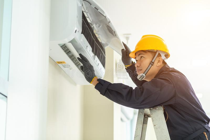 Male technician repairing air conditioner safety uniform indoors stock photo