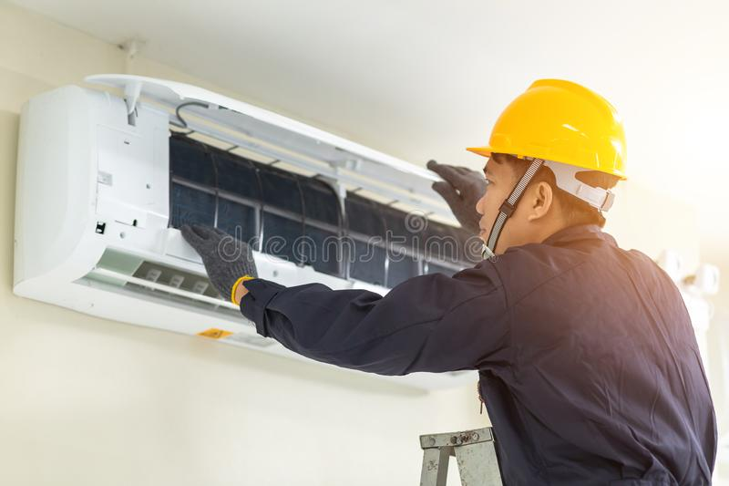 Male technician repairing air conditioner safety uniform indoors royalty free stock image
