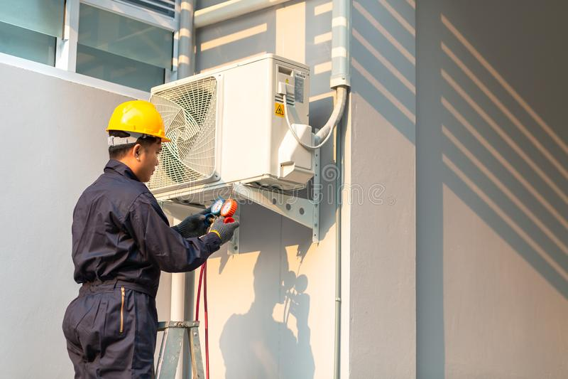 Male technician repairing air conditioner safety uniform, Technician vacuum pump evacuates and checking new air conditioner royalty free stock images