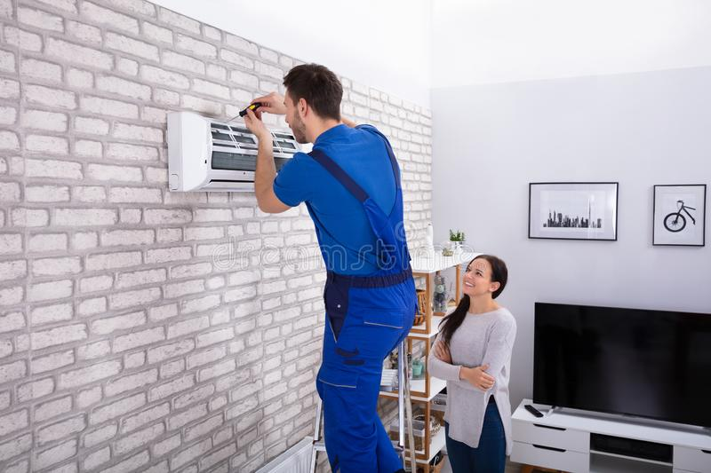 Male Technician Repairing Air Conditioner With Screwdriver. Smiling Woman Looking At Male Technician Repairing Air Conditioner With Screwdriver In Home royalty free stock image
