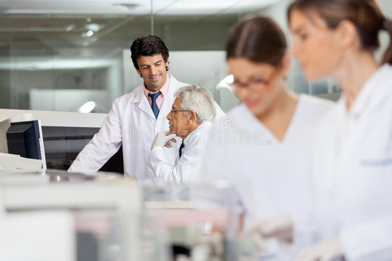 Male Technicians Discussing In Lab. With female colleagues working in foreground royalty free stock images