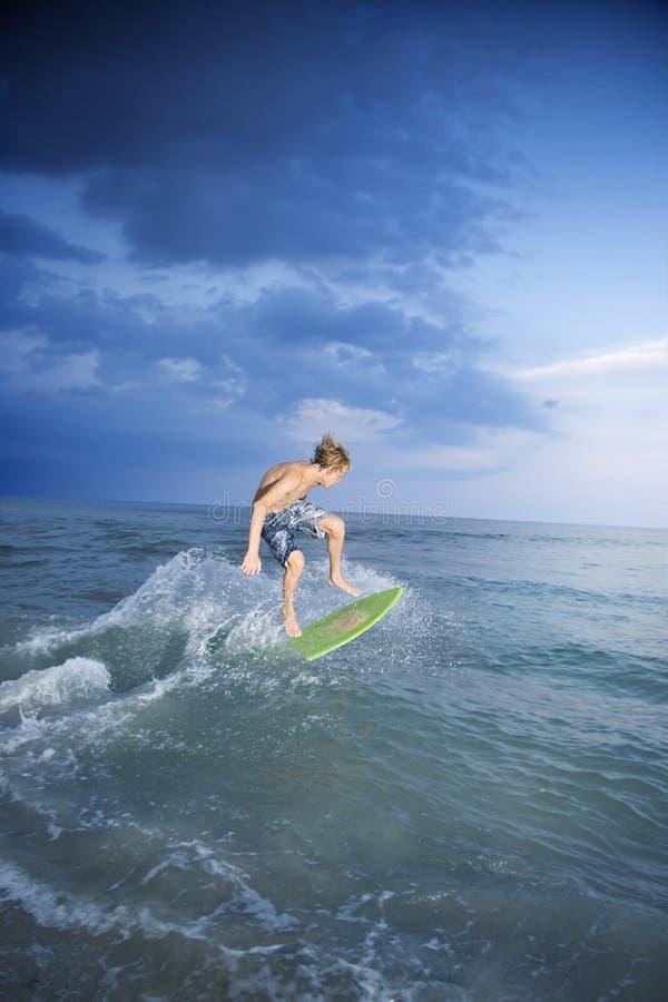 Male teen riding skimboard. royalty free stock photos