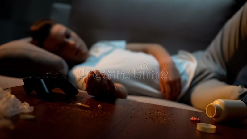 Male teen sleeping in messy room, cigarette and pills on table, game addiction stock photo