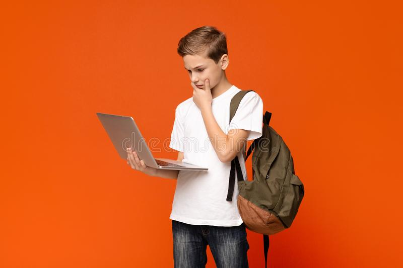 Male teen student concentrating, working on his laptop. Computer, orange studio background stock photo