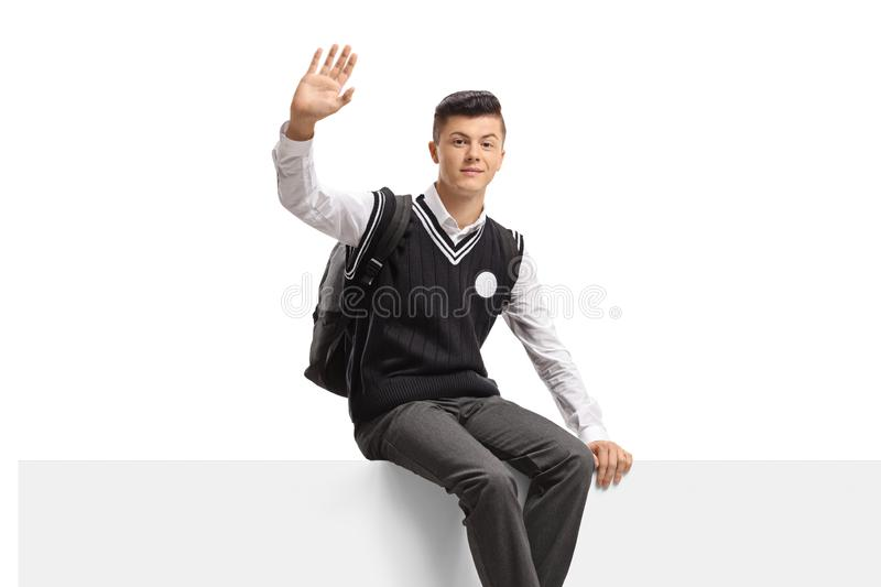 Male teenage student in a uniform sitting on a panel and waving at the camera stock photos