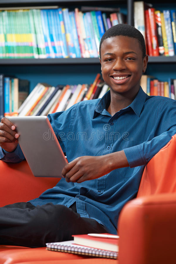 Male Teenage Student Using Digital Tablet In Library. Male Teenage Student Uses Digital Tablet In Library stock photo