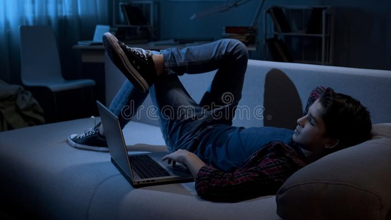Male teenager addicted to gadgets lying on sofa and surfing in internet, laptop royalty free stock images