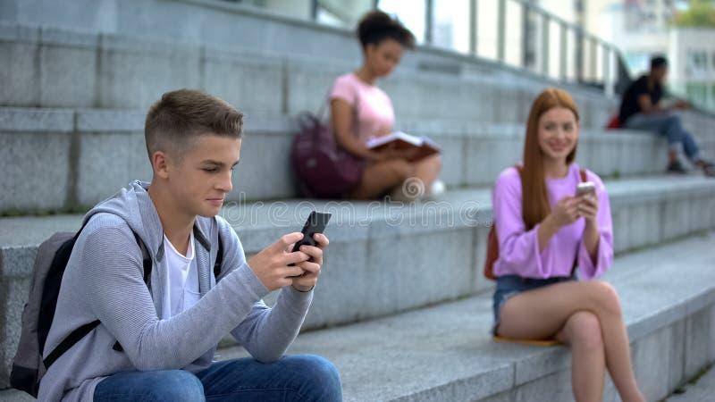 Male teenager chatting smartphone sitting beside classmate, online communication. Stock photo stock image