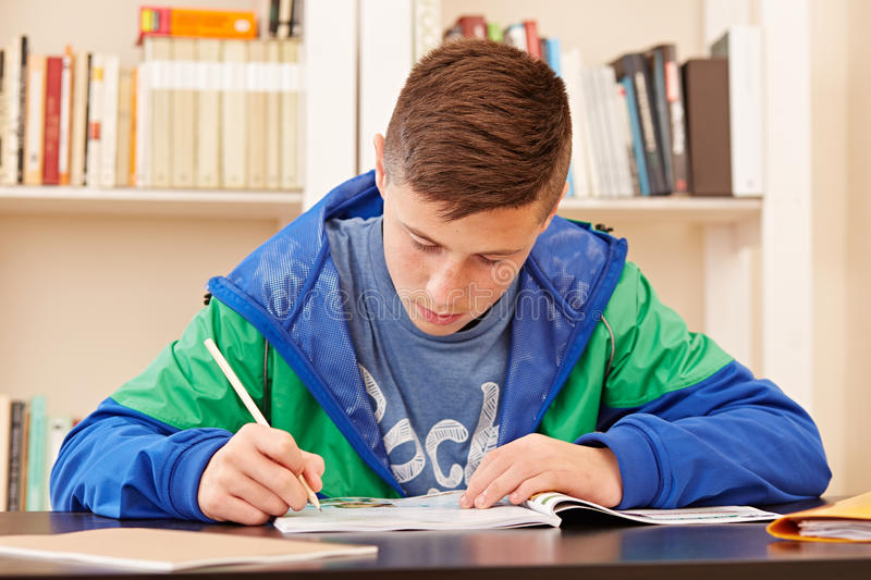 Male teenager concentrated doing homework stock images